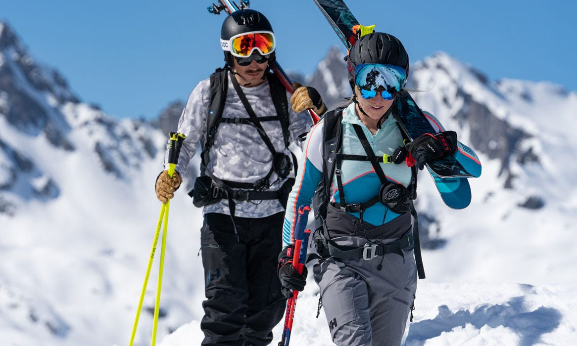 Professional skiers wearing HH base layers whilst hiking up a mountain