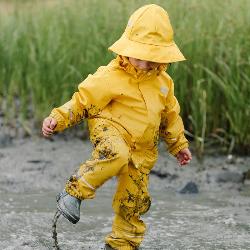 Kid splashing in the rain wearing Helly Hansen waterproof clothing