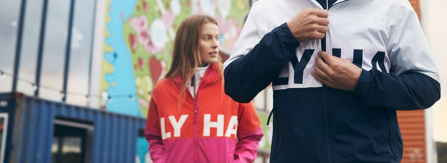 Man and woman wearing Helly Hansen jackets in an urban setting