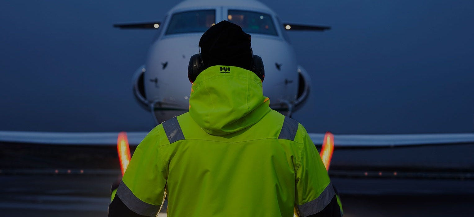 Industry worker wearing Helly Hansen Workwear hi vis directs a plane on the tarmac