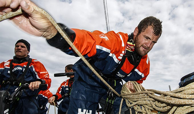 member of team ericsson in the volvo ocean race adjusts rope