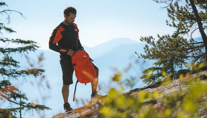 Man standing on mountain ridge wearing Helly Hansen base layer.