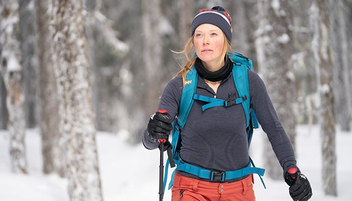 Woman backcountry ski touring through a forest, wearing a Helly Hansen base layer.