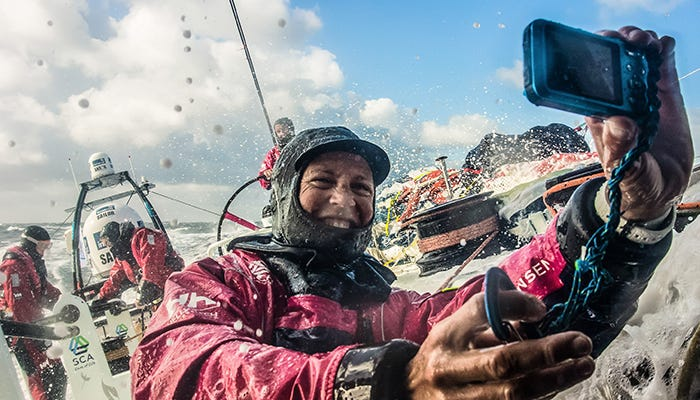 a sailor smiles amidst splashes in the volvo ocean race