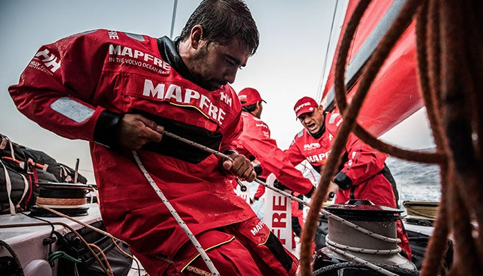 A member of Team MAPFRE in the Volvo Ocean Race pulls hard on a rope