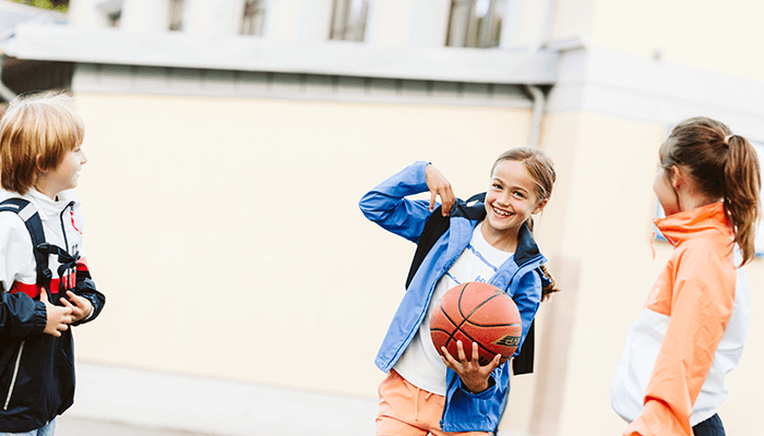 kids holding a basketball at the court