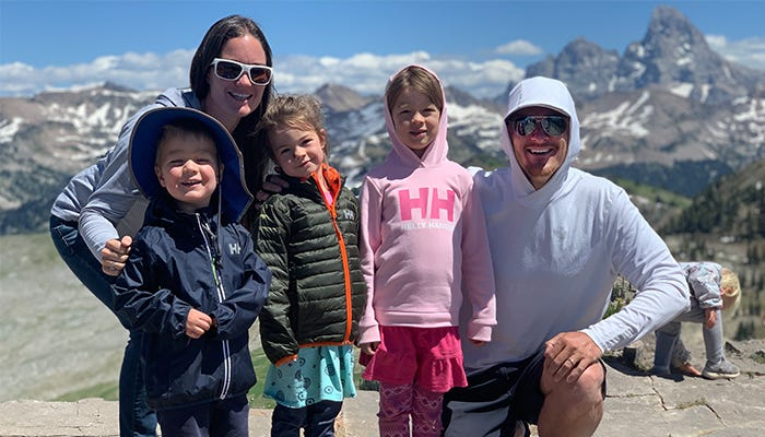 Family poses for photo in front of mountain range.