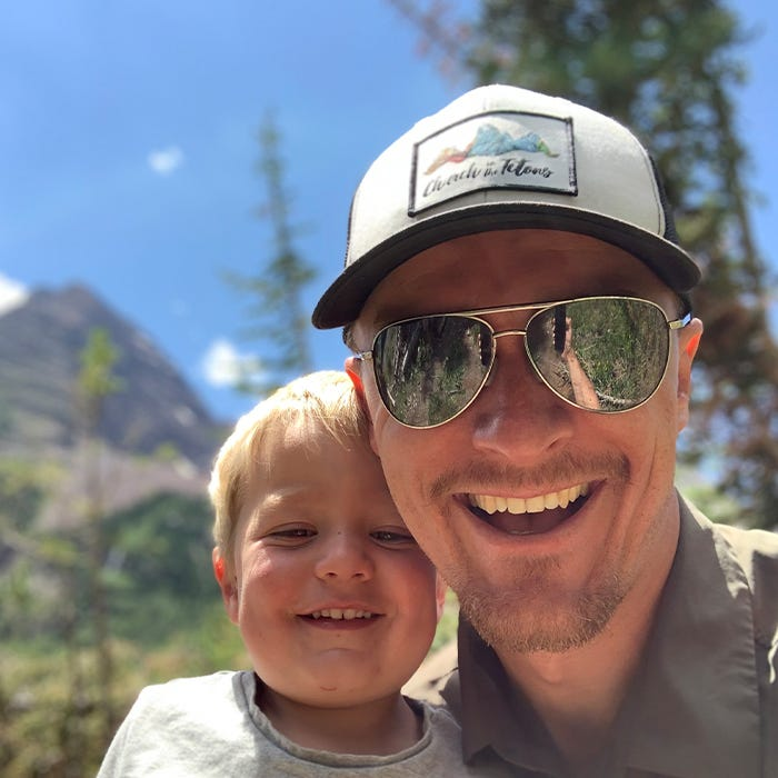 Father and toddler son smile for selfie photo.