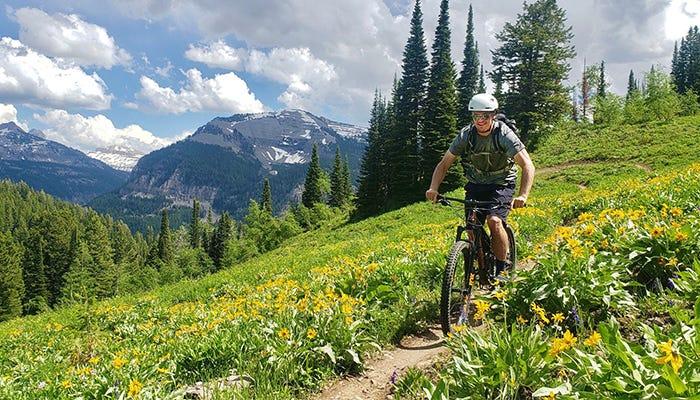 Man rides mountain bike down trail in mountain range.