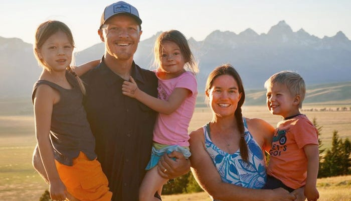 Family standing for photo op in front of mountain range.