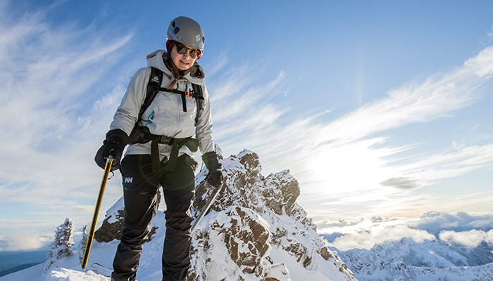 Mountaineer standing on top of a snow-capped mountain peak.