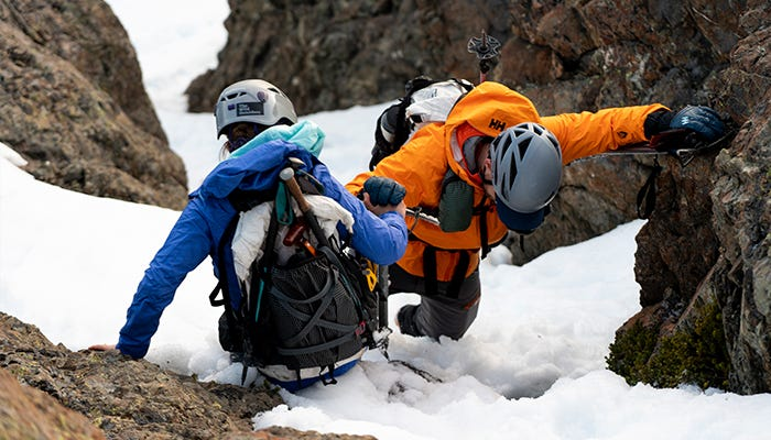 Man and woman working as a team to climb, near the peak.