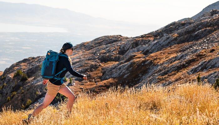 hiker strides across field.