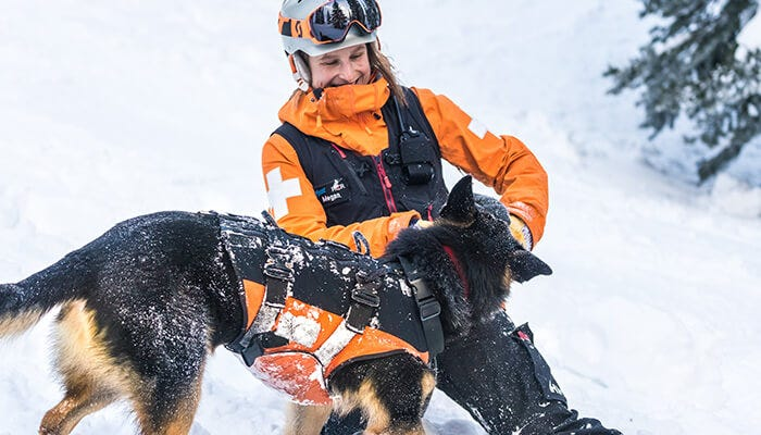 ski patroller and dog in the snow