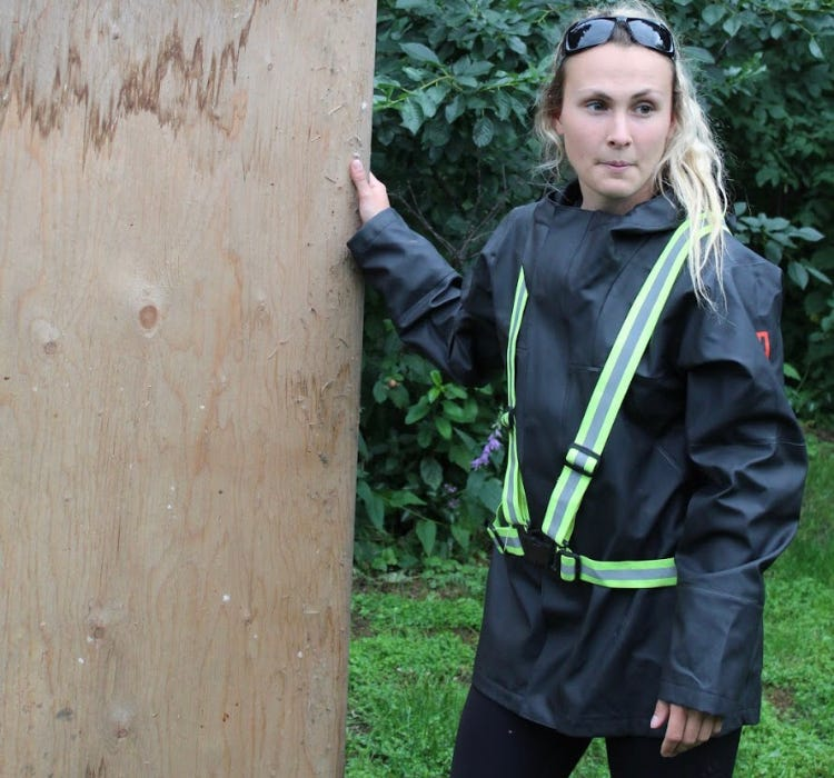 Woman standing next to plywood board.