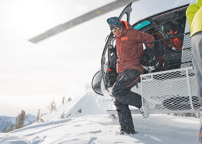 Skier steps out of helicopter onto snow.