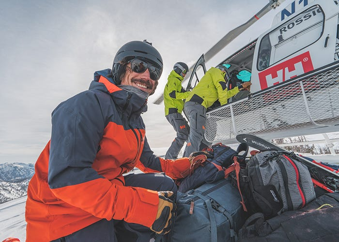 Skier smiles at camera near helicopter.