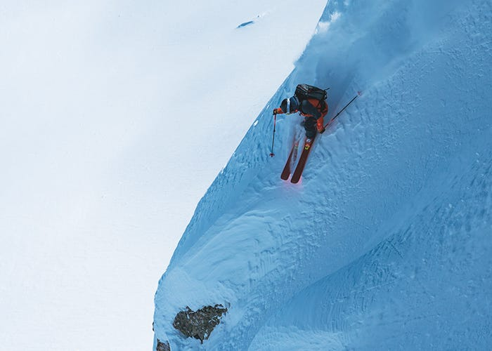 Skier rides down line of light and shadow.