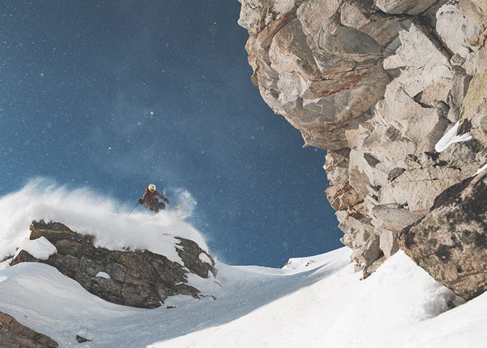 Skier floats out over edge of small cliff drop, coming down the mountain.