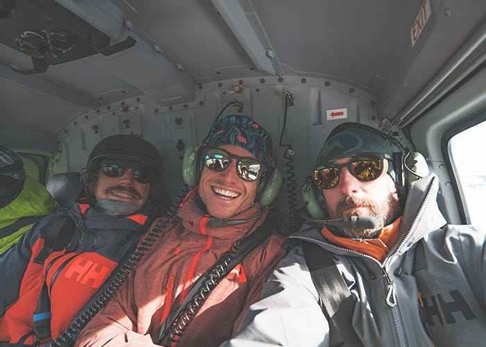 Two skiers and a photographer pose for a group selfie inside the helicopter cockpit.