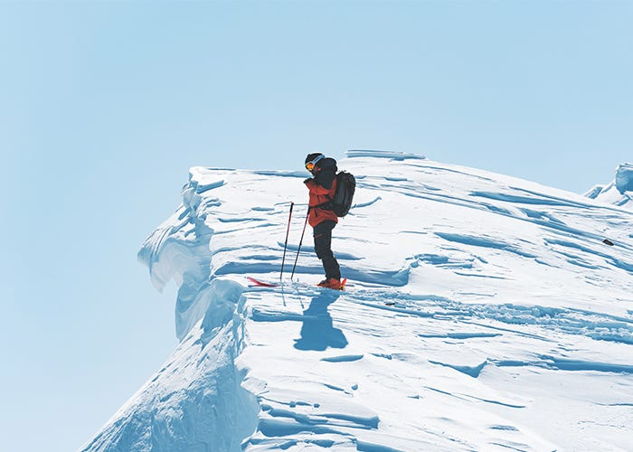 Skier looks out over edge of mountain.